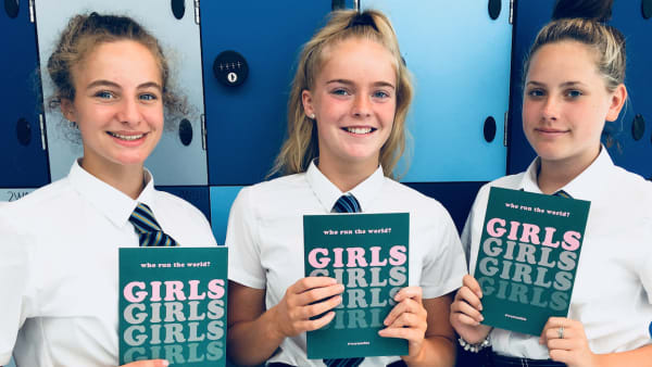 Image of three The Girls Network ambassadors holding notebooks and smiling